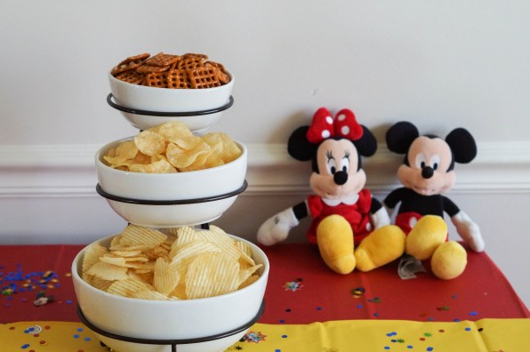 Chips and pretzels in white bowls next to stuffed Mickey and Minnie Mouse.