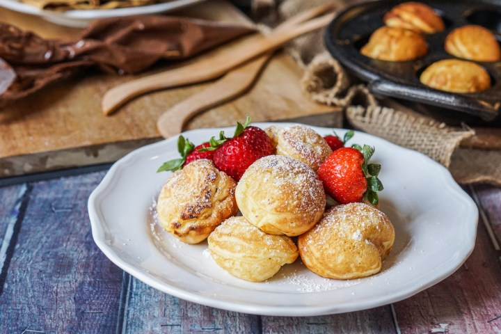 Nutella Stuffed Aebleskiver on a white plate with strawberries and topped with powdered sugar. Piping bag filled with Nutella and Aebleskiver pan in the background.
