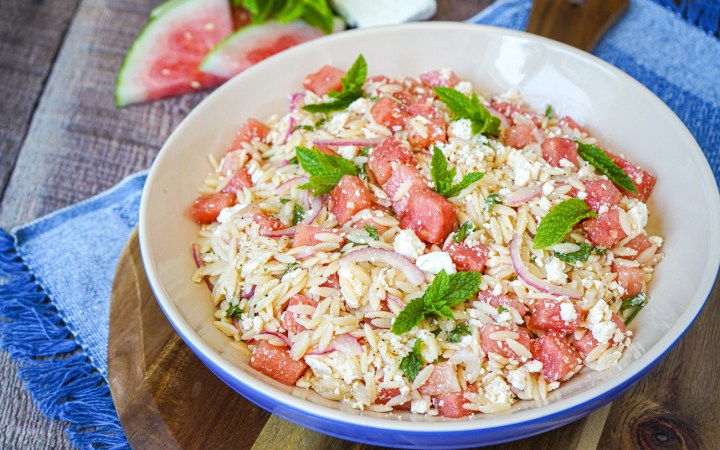 Watermelon Feta Orzo Salad in a large blue bowl on a round wooden board.