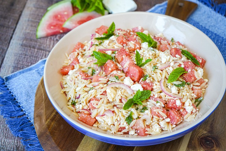 Watermelon Feta Orzo Salad in a large blue rimmed bowl on a round wooden board.