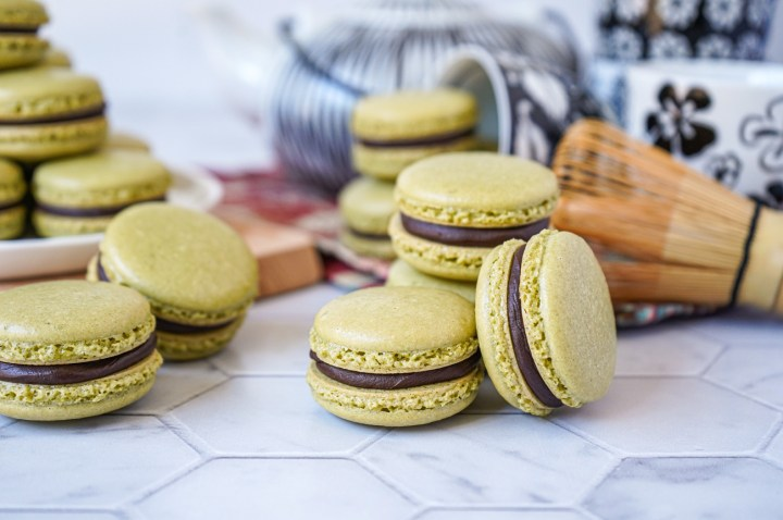 Stacks of Matcha Macarons with Chocolate Ganache in front of a black and white tea set.