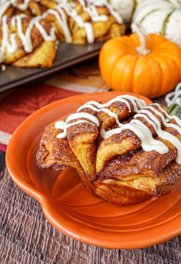 Close up of Pumpkin Cinnamon Fantail Rolls on a pumpkin plate and in muffin tin next to pumpkins.
