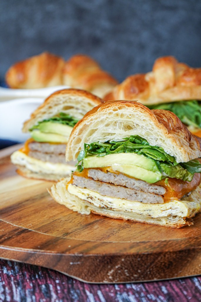 Side view of Croissant Breakfast Sandwich cut in half to show the layers.