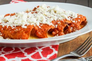 Side view of Enchiladas Rojas de Queso (Red Enchiladas with Cheese) on a white plate with two metal forks in front.