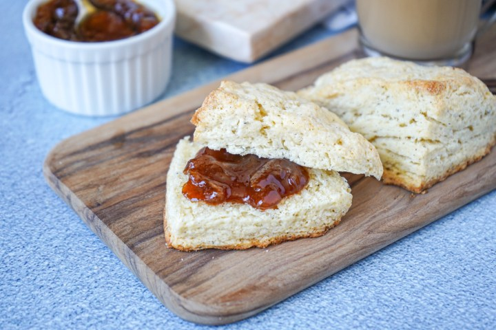 Two Cardamom Vanilla Cream Scones on a wooden board with one filled with blood orange jam.