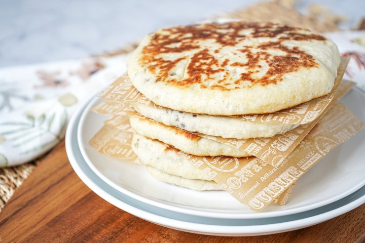 Stack of five Hodduk (Korean Sweet Fried Pancakes) on a white plate.
