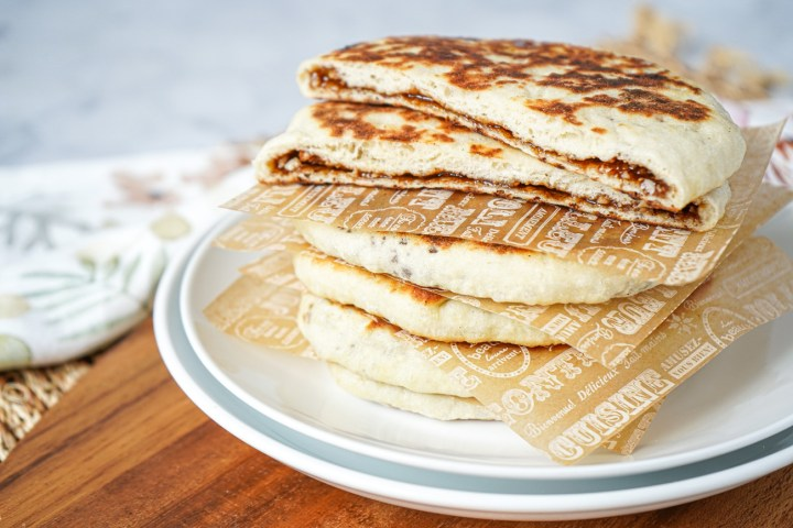 Stack of five Hodduk (Korean Sweet Fried Pancakes) with the top one cut to show the filling.