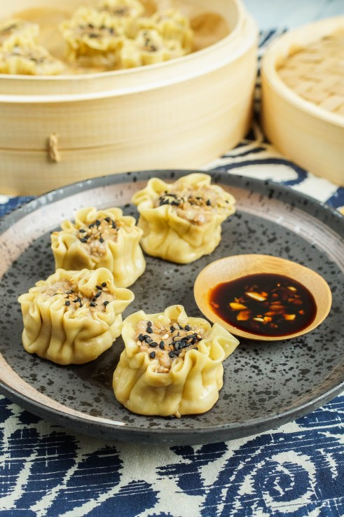 Four Shumai (Pork and Ginger Dumplings) on a brown plate with dipping sauce and a steamer basket in the background.