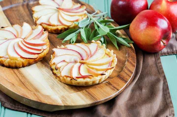 Three Apple and Caramelized Onion Tarts on a wooden platter next to a bunch of sage and three apples.