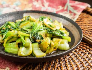 Baby Bok Choy with Ginger and Garlic on a dark brown plate.