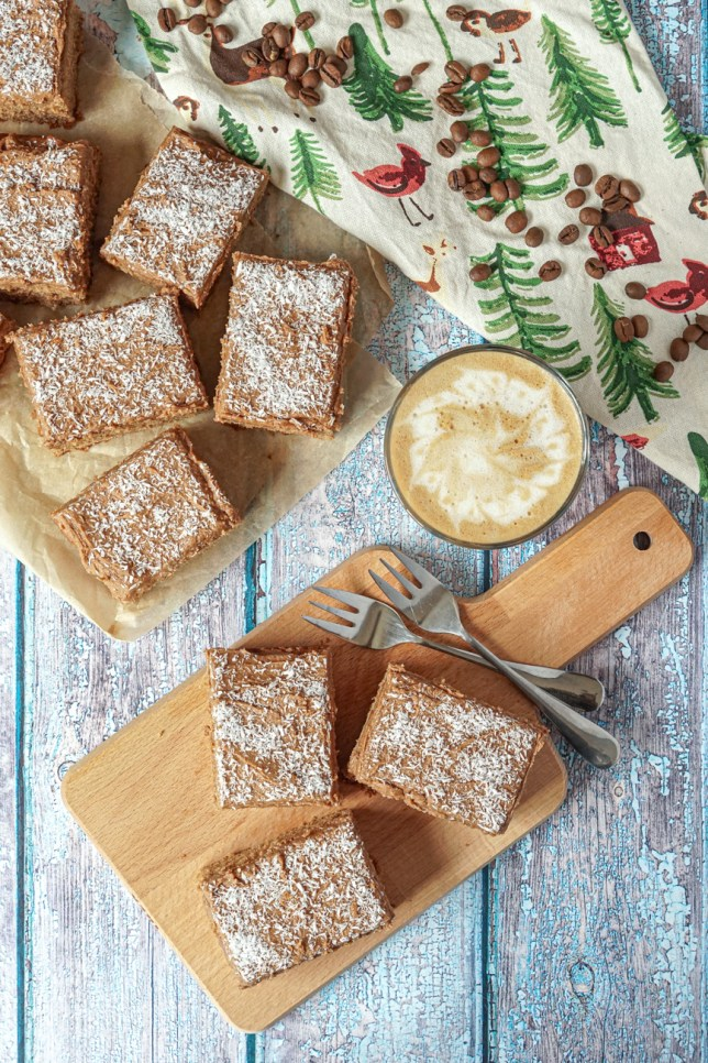 Aerial view of Kärleksmums (Swedish Coffee Cake)- three on a wooden board next to two silver forks and a latte. Six more slices are on a piece of brown parchment next to a towel with green trees and topped with a few coffee beans.