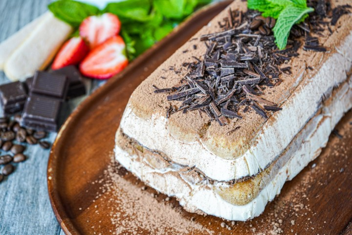 Semifreddo al Tiramisù (Tiramisu Semifreddo) on a wooden board next to chocolate, strawberries, and mint.
