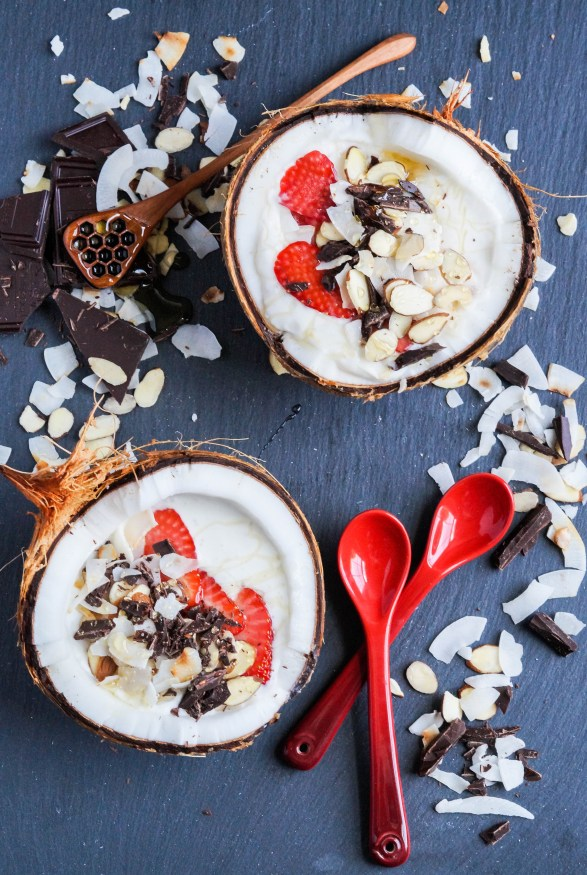 Aerial view of Coconut Smoothie Bowl in two halved coconuts next to two red spoons.