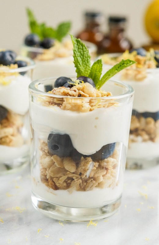 Close up of Lemon Blueberry Parfait in a glass with yogurt, granola, blueberries, and fresh mint.