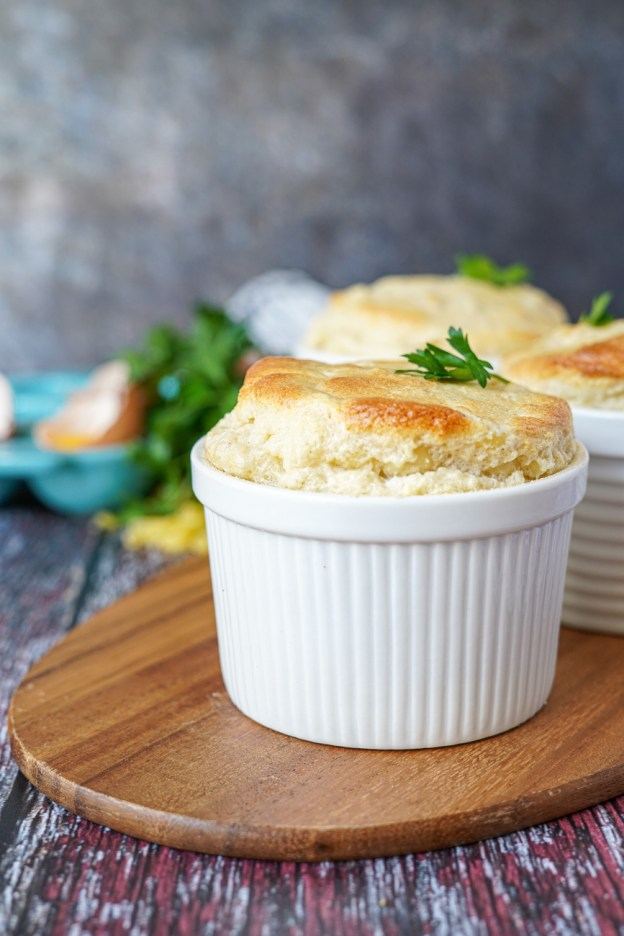 Side view of Macaroni and Cheese Soufflé in a white ramekin and topped with a parsley leaf.
