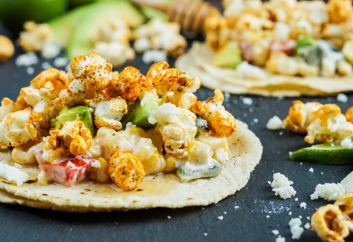 Close up of Popcorn Tacos with crumbled cheese and avocado in the background.