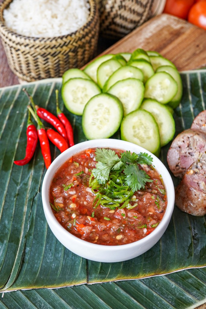 Jeow Mak Len (Lao Tomato Dipping Sauce) in a white bowl next to chilies, cucumber, rice, and sausage.