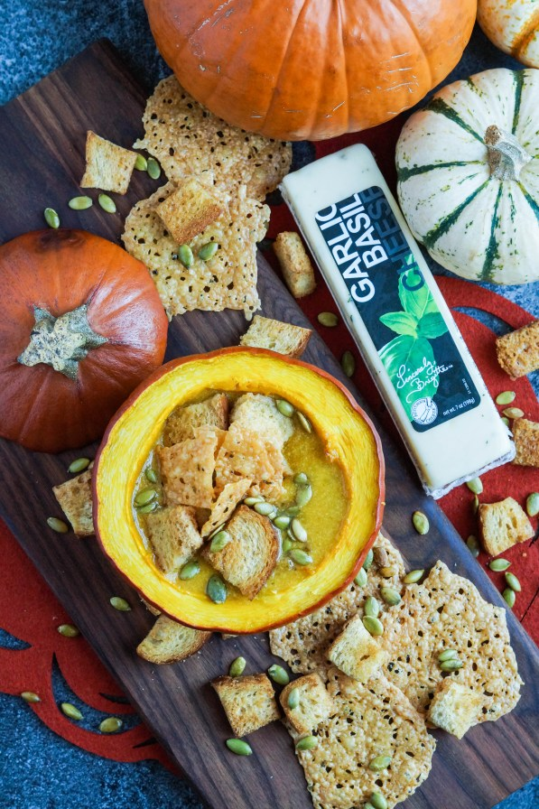 Aerial view of Pumpkin Cheese Soup with Garlic Basil Cheese Crisps in a roasted pumpkin on a wooden board.