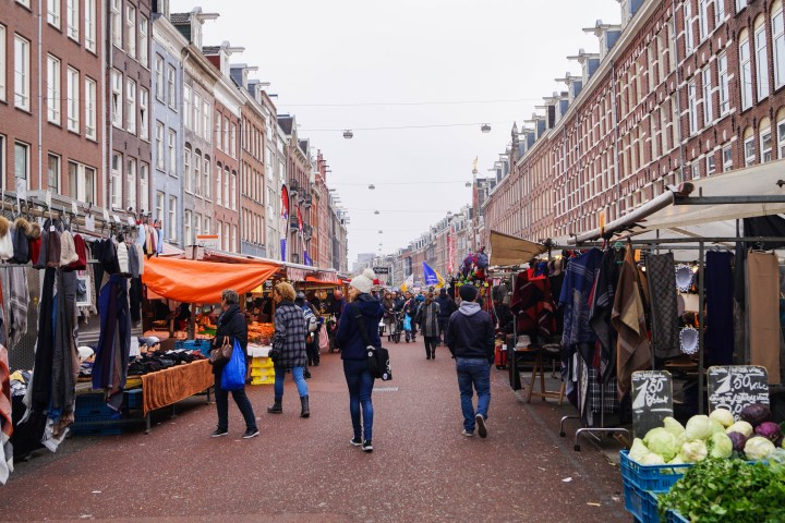 Walking down Albert Cuyp Markt with people and stalls against large brown buildings.