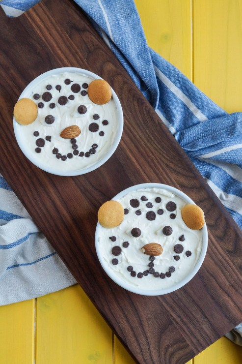 Aerial view of two Cheetah Cheesecakes in white ramekins on a wooden board over a blue and white striped towel.