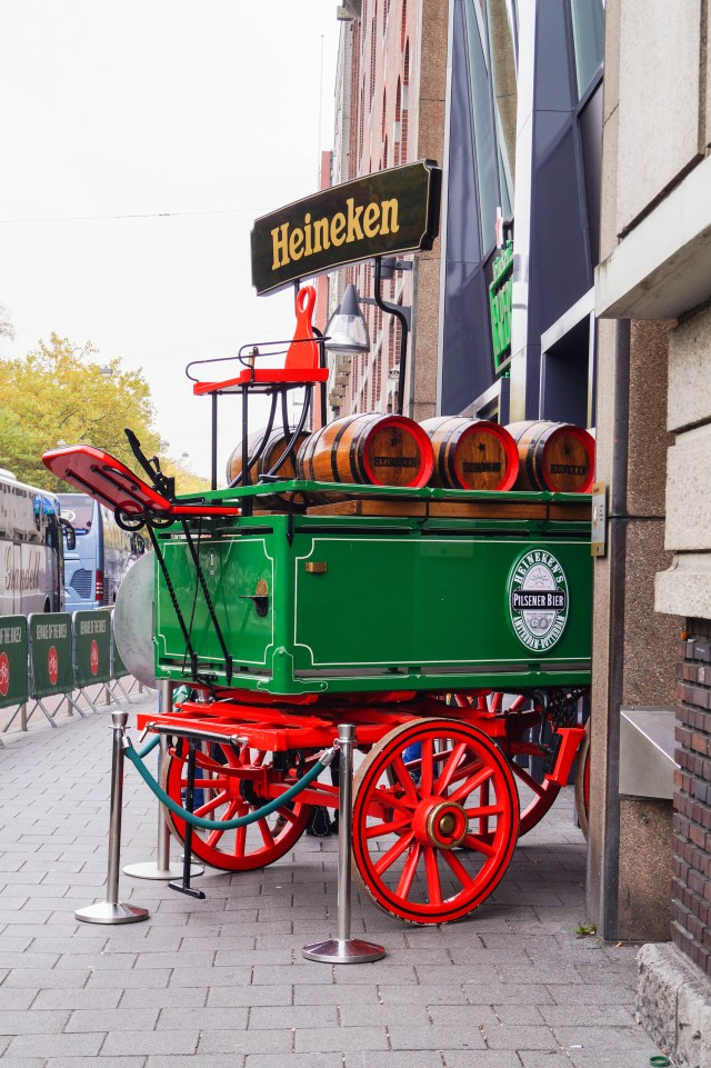 Outdoor entrance to The Heineken Experience with large green cart with red wheels and barrels.