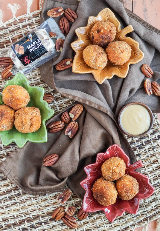 Aerial view of Sweet Potato Maple Pecan Goat Cheese Croquettes on three leaf plates next to a brown towel, mustard dipping sauce, and pecans.