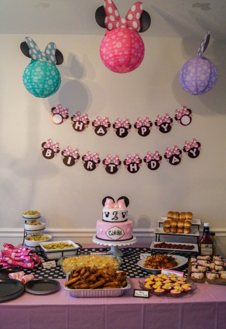 Minnie Mouse Lanterns hanging over a pink table with food and cake.