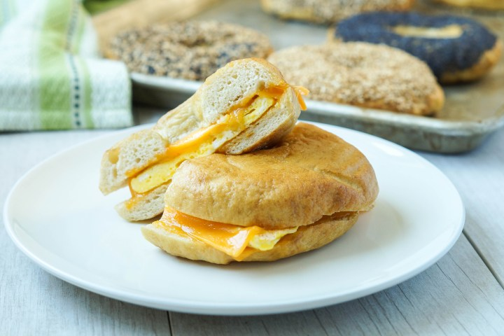 Egg and Cheese Bagel Sandwich with more bagels on a baking sheet in the background.