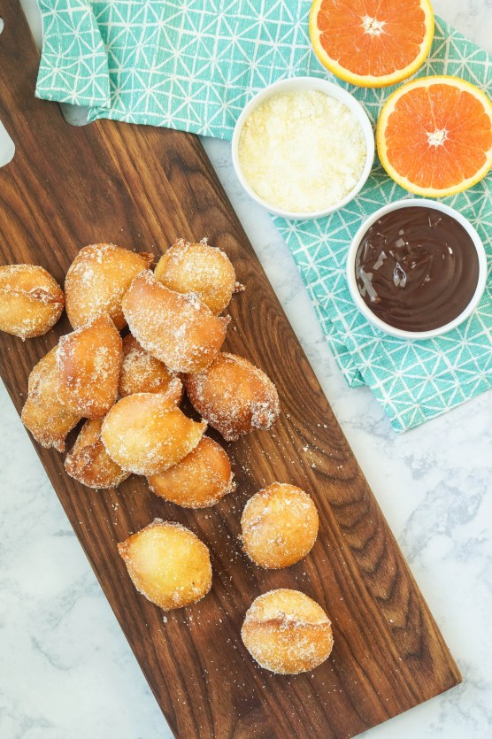 Aerial view of Buñuelos with Brown Velvet Glaze on a wooden board next to two orange halves.