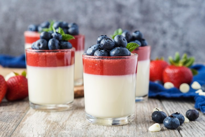 Strawberry and White Chocolate Panna Cotta in clear glasses topped with fresh blueberries and a sprig of mint.