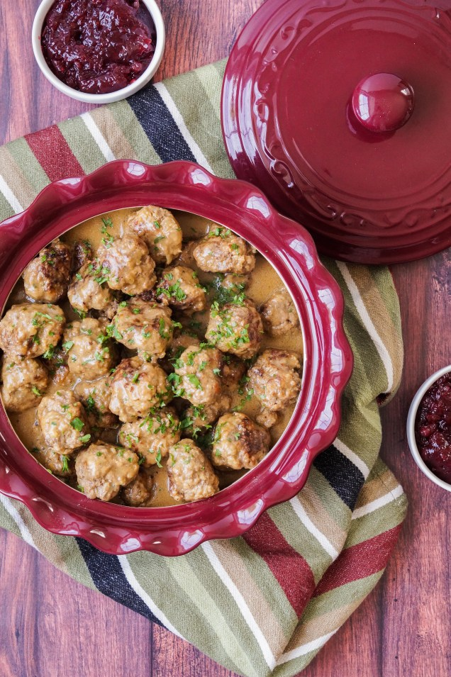 Aerial view of Swedish Meatballs in a maroon dish resting on a red/green/white/dark blue striped towel next to two small white bowls of lingonberry jam.
