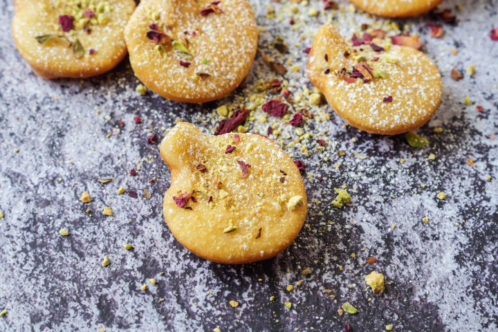 Scattered Afghani Gosh-e-Fil (Elephant Ear-Shaped Fried Pastry) topped with rose petals and crushed pistachios.