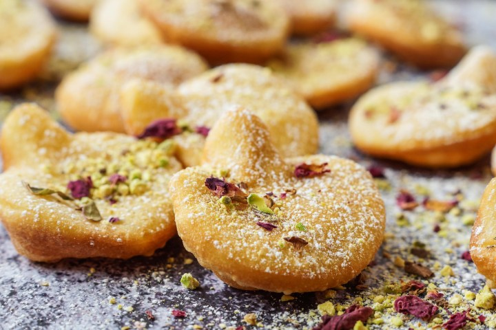 Close up of Afghani Gosh-e-Fil (Elephant Ear-Shaped Fried Pastry) topped with rose petals and crushed pistachios.