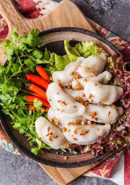 Arial view of Pan Sip Nueng Sai Kai (Thai Steamed Dumplings with Chicken-Peanut Filling) on a brown plate with lettuce, red chillies, and cilantro.