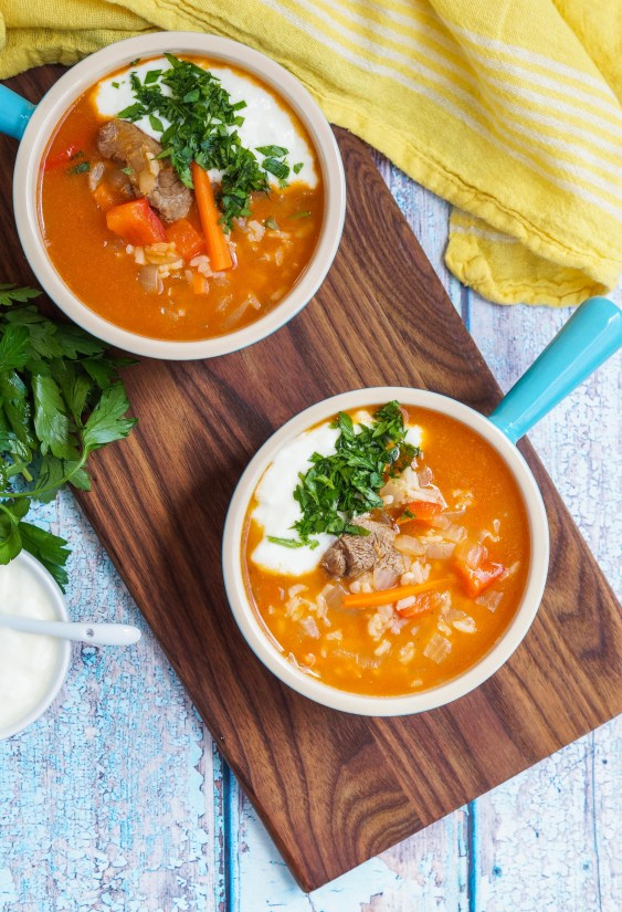 Aerial view of Qatiqli Hu'rda (Uzbek Rice Soup) in two bowls with yogurt and parsley.