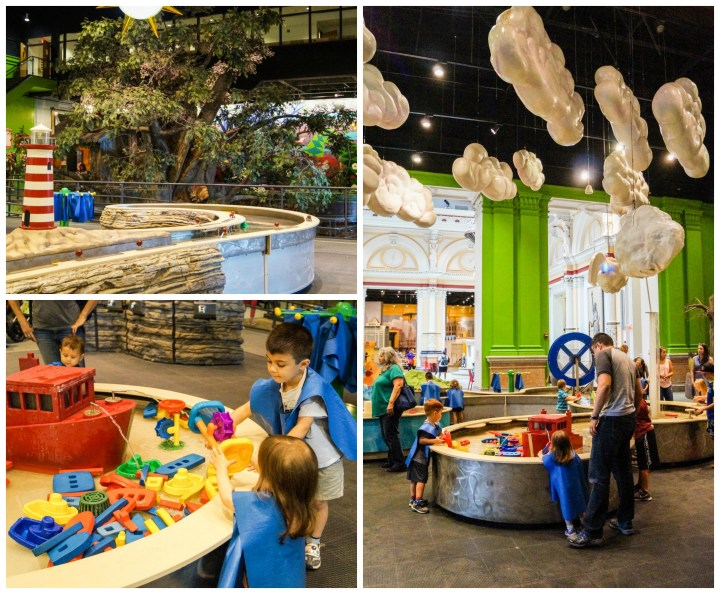 River Adventures exhibit at the Please Touch Museum with water toys and clouds hanging from ceiling.
