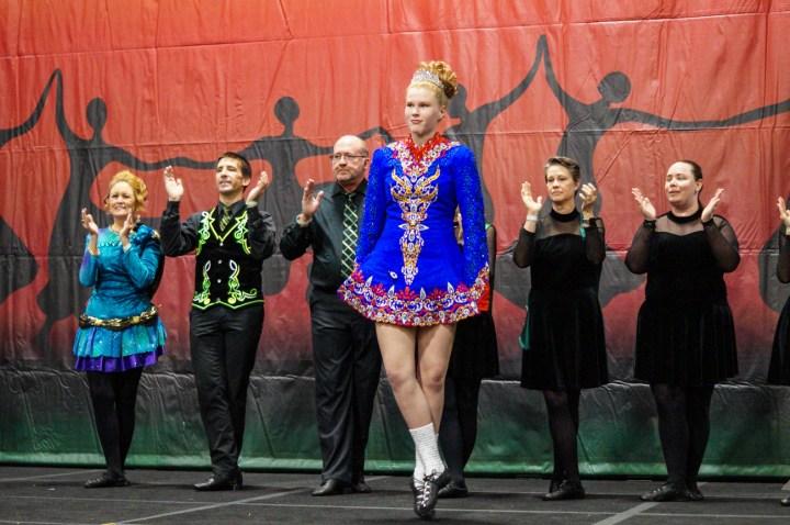 O'Neill James School of Irish Dance group dancing in traditional Irish costumes- blue, black, and black/green.