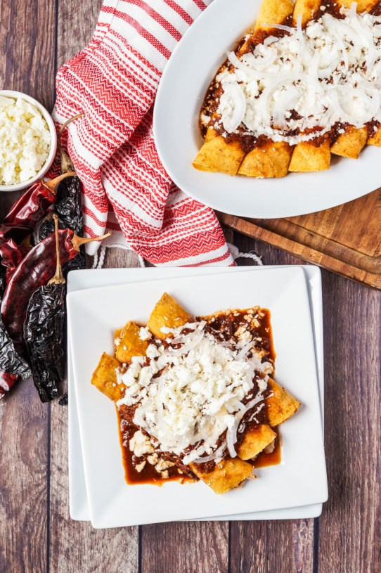 Aerial view of Enchiladas Rojas on two stacked white plates with more next to them on a white platter.