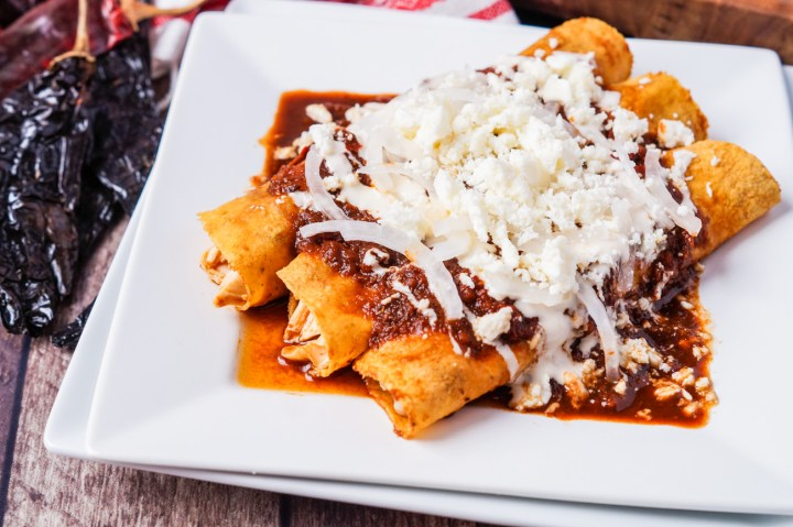 Enchiladas Rojas on a white plate and topped with red Guajillo Pasilla sauce, sliced onions, crema, and crumbled queso fresco.