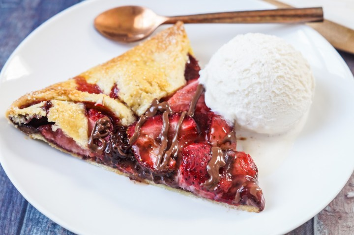 Slice of Strawberry Nutella Galette on a white plate with a scoop of vanilla ice cream and a copper spoon.