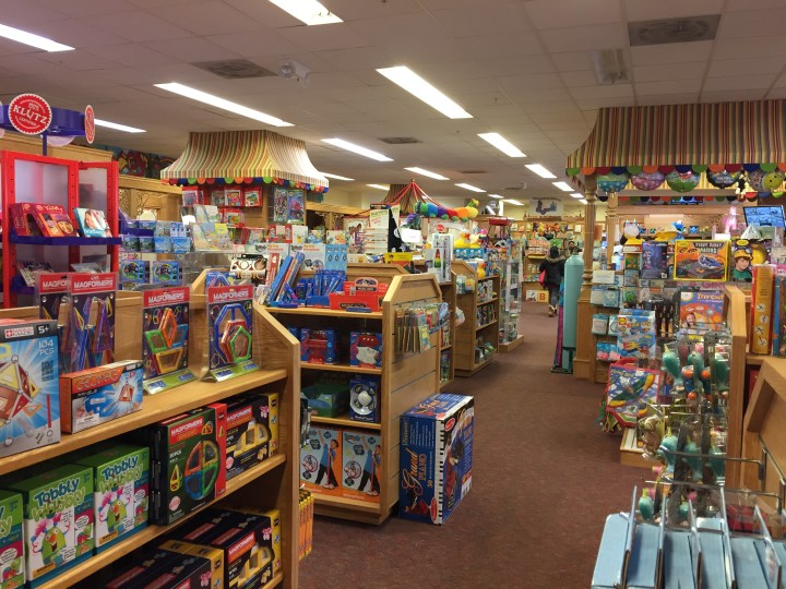 View inside Kinderhaus Toys with shelfs of toys on display.