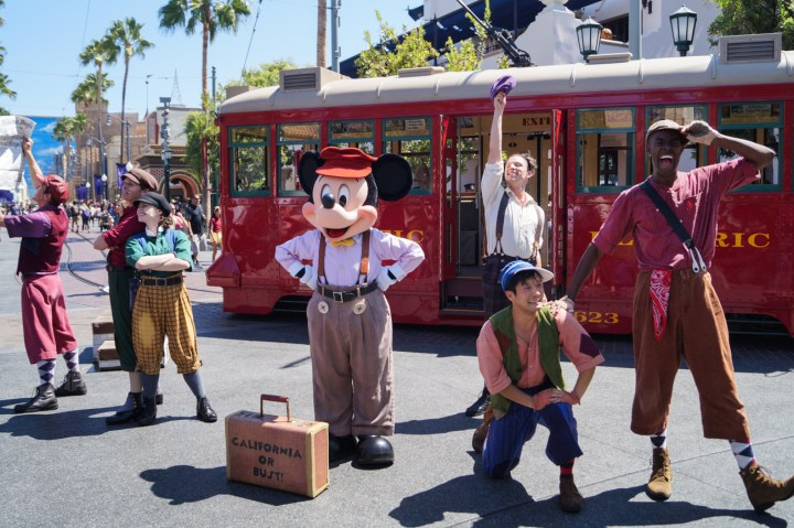 Mickey Mouse wearing suspenders in front of a red trolley with dancers