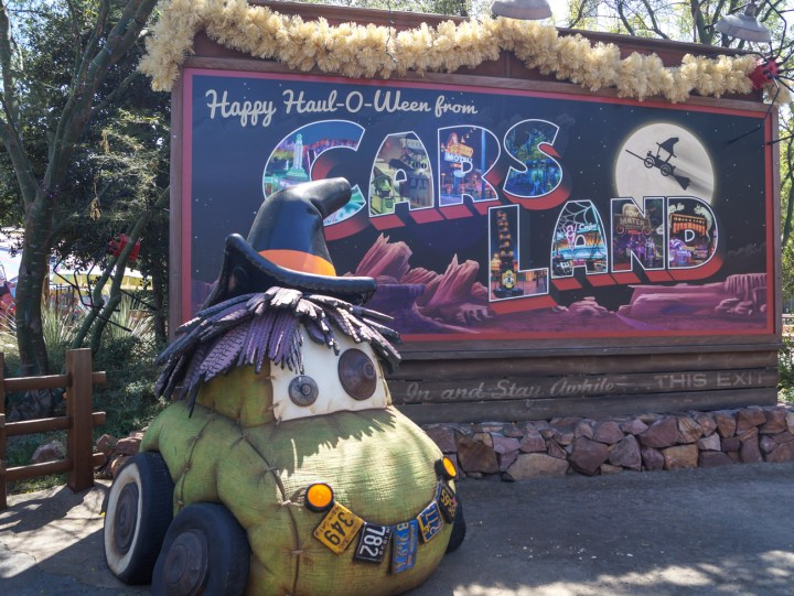"Car decorated for halloween with Witch's hat in front of sign stating ""Happy Haul-o-Ween from Cars Land"""