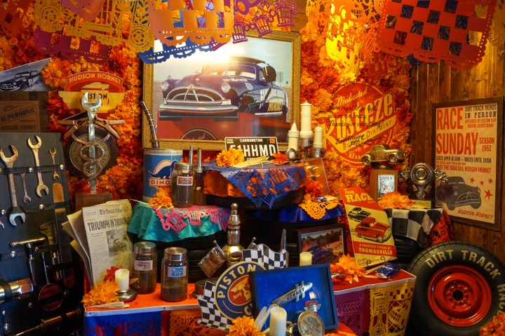 Ofrenda in Cars Land for Doc Hudson- tires, wrenches, Rust-eze sign, and photo of the car