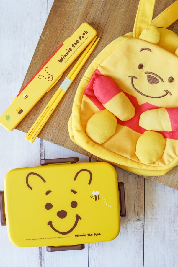 Winnie the Pooh Bento Box products- Winnie the Pooh box with a yellow cover and Winnie the Pooh's face, yellow chopsticks, and a small Winnie the Pooh bag to hold the bento box.