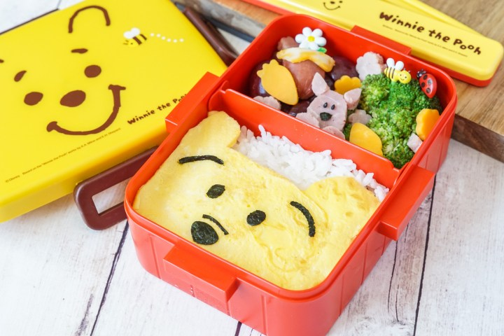 Winnie the Pooh Bento Box (container has a red bottom and yellow top with Winnie the Pooh's face) filled with rice topped with an egg crate with Winnie the Pooh's face made of nori. The other section has broccoli, cheese cut into carrots and flowers, hot dog piece shaped like a hunny pot, and piglet made of small ham pieces.