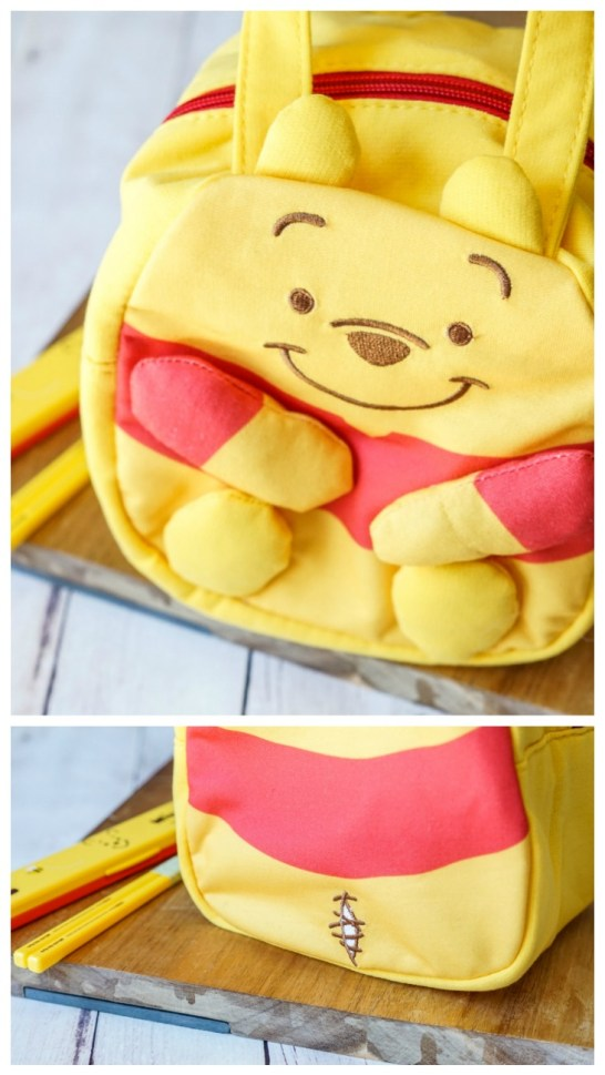 Small bag shaped like Winnie the Pooh with a red shirt and a small ripped stitch design on the back.