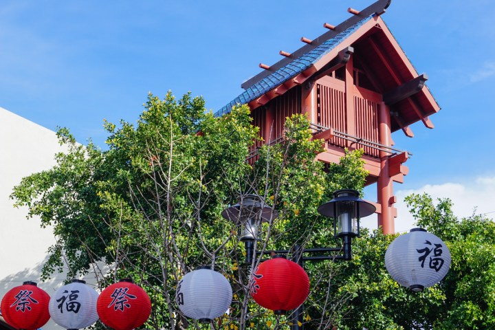 Red and white round lanterns on a string in front of trees and a red tower.