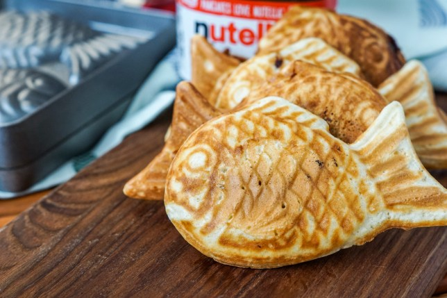 Four Nutella Taiyaki (Fish shaped pastries) on a wooden board with taiyaki pan in the background.