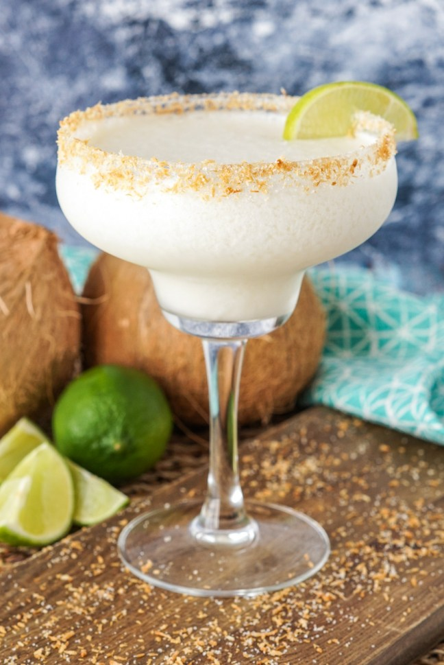 Frozen Coconut Margarita in a tall glass with toasted coconut rim and lime wedge.